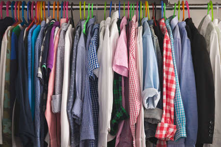 Close-up of hangers with different fashionable clothes. Children's clothes of different colors are hung on hangers in the wardrobe room. Shirts, T-shirts and other children's clothing 스톡 콘텐츠 - 130401058