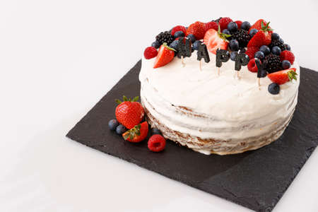 Celebratory cake on a white glass table. Layered cream vanilla cake decorated with berries of raspberry, strawberry and blueberry. The letters of the candle HAPPY stuck in the cake. Festive concept