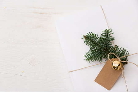 Top view on Christmas or New Years gift decorated with a spruce twig, tag and bell. A gift wrapped in white stylish paper lies on a white wooden table. Festive and Christmas concept