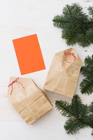 Stylish gifts for Christmas or New Year lying on a white wooden table surrounded by fir branches. Gifts are packaged in craft packages and decorated in the form of houses. Christmas Gift Ideas