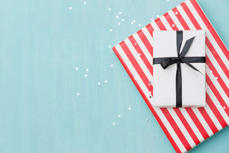 Top view of gifts lying on a blue wooden background. Stylish striped gift and a gift wrapped in white paper tied with a black ribbon. Silver stars are scattered on the table like confetti. 스톡 콘텐츠 - 130401299
