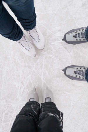 Top view on the feet in skates in casual wear on the ice. Family, mom, dad and son skate on a winter day. Winter fun. 스톡 콘텐츠 - 130401297
