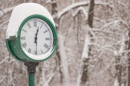 Closeup of clock in the park on the background of trees. On the clock is a thick layer of snow. The symbol of the coming year and Christmas. Holiday concept