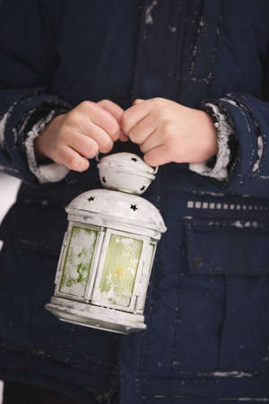Christmas lantern in the hands of a boy. Winter, a little boy on the street shines a lantern. Winter and christmas concept