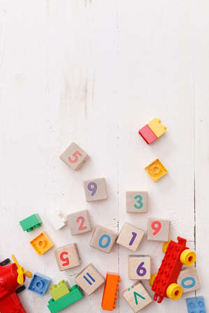 Wooden cubes with colorful numbers 2019. Educational cubes made of plastic, car and other toys. The early development of the child. Directly above 스톡 콘텐츠 - 131784010