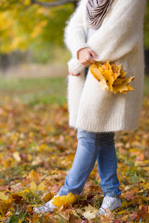 Young woman with maple leaves. Girl walking in the park and enjoying spring colors. Lifestyle and autumn concept.