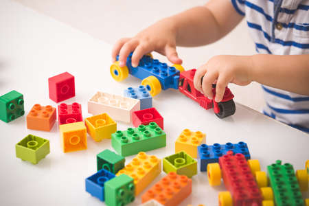 Toddler child playing multi-colored cubes on the table. Colorful plastic bricks for the early development of the child. Early learning and educational toys for a little boy 스톡 콘텐츠 - 131784384