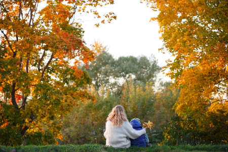 Mom with her son are sitting on the grass against the backdrop of an autumn sunset. Family walking in the park and enjoying sunny weather. Lifestyle and autumn concept. 스톡 콘텐츠