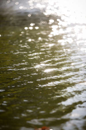 Beautiful view of the water surface with highlights. Breath of autumn. Reflection of sun glare in river or lake waves 스톡 콘텐츠