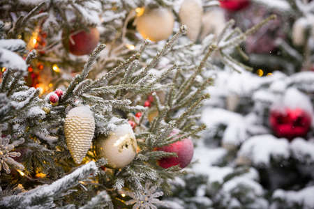 Beautiful decorated Christmas tree with real snow. Red and gold balls and a garland with lights with flashlights. Winter holiday. Lighting design