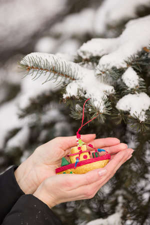 Homemade Christmas toy in the hands of the girl on the background of the Christmas tree. Seasonal holidays and celebrations. Traditional New Year and Christmas decor.