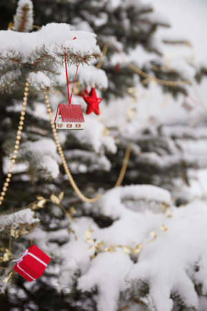 Christmas decorations on a beautiful tree coated with snow. Traditional christmas tree. Holiday and celebration concept 스톡 콘텐츠 - 132133686