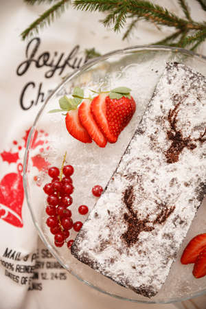 Homemade Christmas chocolate cake sprinkled with powdered sugar. The cake is decorated with red currants, strawberries and icing sugar. Holiday concept. 스톡 콘텐츠