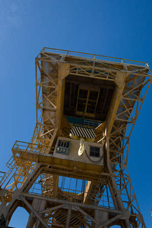 Bottom view of a large specialized dam crane against a clear blue sky with particles water steam. The old crane is in perfect condition to ensure safety on the dam