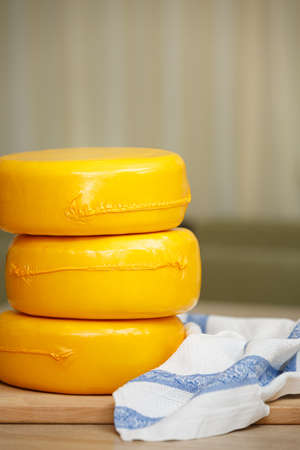 Three heads of cheese in a yellow vacuum pakage on a cutting board. Homemade cheese service. The concept of nutrition and healthy lifestyle. 写真素材