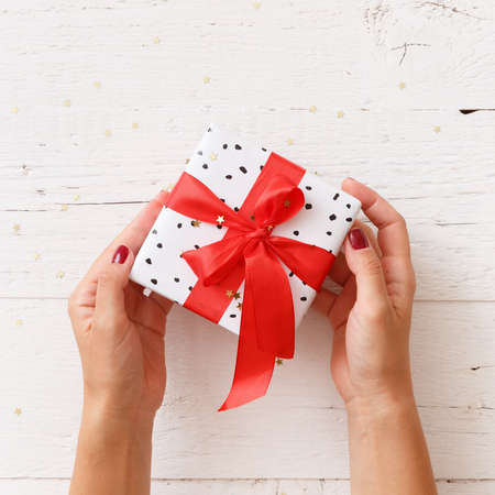 Closeup of girls hands holding a beautifully wrapped Christmas or birthday gift box with a red satin ribbon on white wooden background.