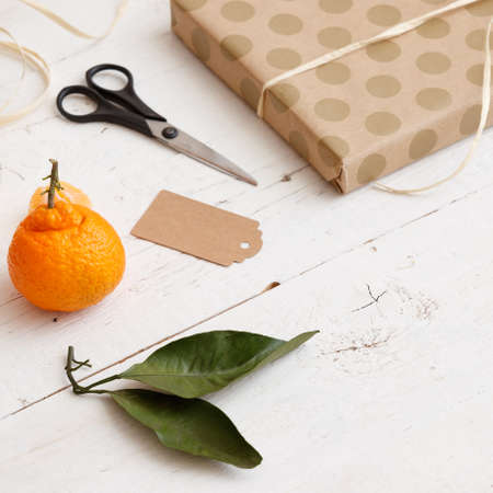 Closeup of a gift wrapped in dotted paper crafts, scissors, ribbon, mandarin and tag on a white wooden background. Gift preparation for the celebration