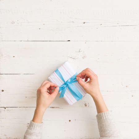 Top view on nicely wrapped Christmas, birthday or any other celebration gift in white paper with blue ribbon in girls hands on white wooden background.