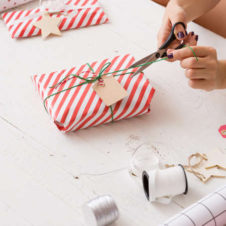 Closeup of young womans hands wrapping Christmas or birthday gift in striped paper and decorating it with and twine and tag. Girl wrapping presents for the party.