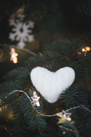A soft knitted heart lies on the branches of a decorated Christmas tree on the background of Christmas decorations and a sparkling garland. Snowflake and star in the background. Holiday season