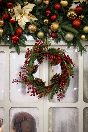 Christmas decorations in the form of an evergreen spruce wreath with red viburnum berries and cones. Garland, Christmas tree branches, artificial flowers and colorful balls over a frozen window.