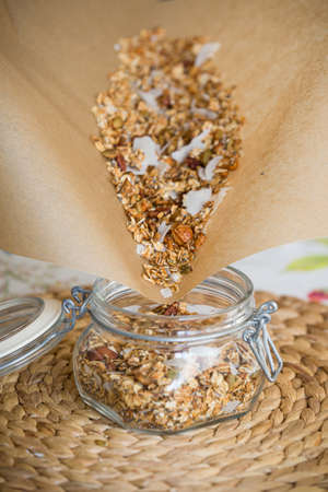 The girl holds baking paper and pours Muesli in a glass jar to the top filled with organic granola with nuts and coconut. A jar of granola is standing on a straw mat. Healthy lifestyle concept.