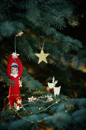 Cute Christmas toy hanging on a garland on the branches of an evergreen Christmas tree on the background of New Year decorations, hanging on the branches of a spruce. New Year and holiday concept