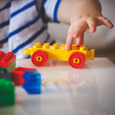 The kid plays with colorful cubes. The child holds in his hand a colored toy with wheels. Early development for children. Home Educational Games Banco de Imagens