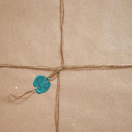 Top view of a parcel wrapped in paper, tied with a cord and sealed with a wax stamp. Stamp with the inscription Good Moments. Gift wrapped in paper.
