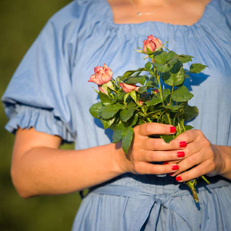 A young girl in a blue dress holds in her hands a beautiful bouquet of garden roses on a sunny day. Girl with a bouquet in the rays of the setting sun. Toning Banco de Imagens