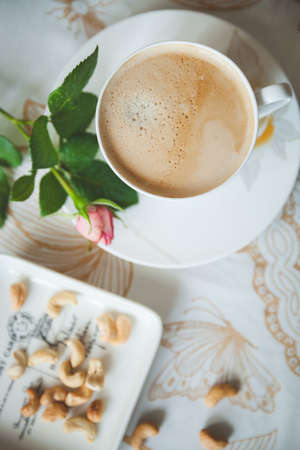 Top view of a tablecloth covered table with a cup of delicious morning coffee and a plate of cashew nuts. Garden rose for mood. Toning