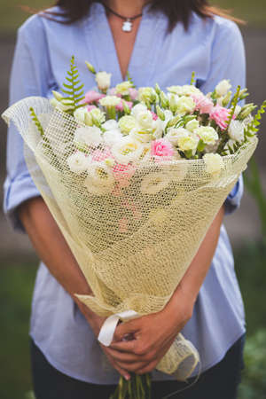 Closeup of a beautiful bunch of beautifully packaged garden roses in womans hands. Girl in a blue shirt with summer flowers on a sunny summer day. Toning 版權商用圖片