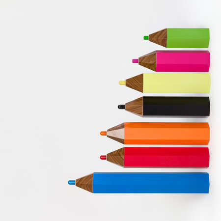 Closeup of multicolored pencils on a white background. Decorative pencils of different lengths. Training, education and development. Banco de Imagens