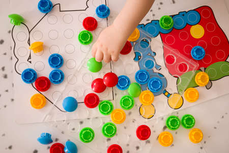 Top view on Kid boy playing multi-colored mosaic parts on the table. Colorful plastic details for the early development of the child. Early learning and educational toys for a little boy 版權商用圖片