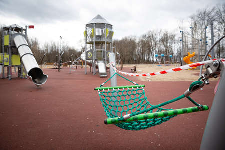 Empty playground with swings in a city park, fenced with warning tapes of red and white. Coronavirus pandemic covid-19 in the world. Stay at home