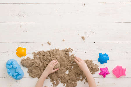 Top view on the hands of a child playing with kinetic sand and tins on a white wooden table background. Learning by playing.