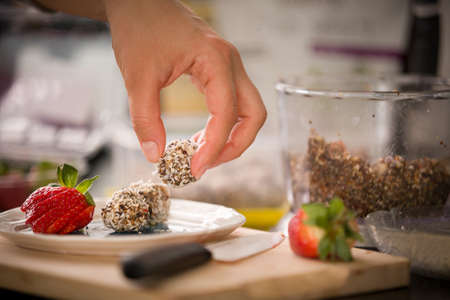 Plate with delicious homemade protein balls in the girl's hand and ripe strawberries. Healthy sweets. Organic raw treats from nuts, coconut, dates and cocoa