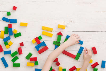 Baby boy or girl play with colorful bricks on a white wooden table. Top view on wooden colorful bricks on a wooden background. School, education and learning concept. Фото со стока