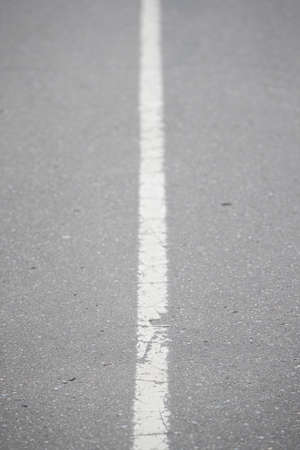 White continuous line on asphalt. Road marking on the highway. Selective focus of the line stretching into the distance. A line dividing the road into two parts.