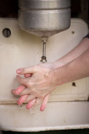 An old rustic washstand hangs on the wall. Metal washbasin with water and a sink for draining water. A man washes his hands. Village Life Concept Stock Photo