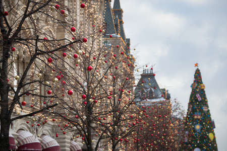 Christmas decorations in the center of New Year's Moscow. Christmas toys hang from fir branches, and garlands sparkle on the building's fa Banco de Imagens