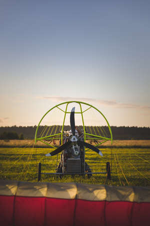 Rear view of a motorized paragliding trolley with a gasoline engine for the pilot and passenger, ready for takeoff. Paralet with a gasoline engine. Flying on a motorized wing. Extreme sports. Paragliding and small aircraft.