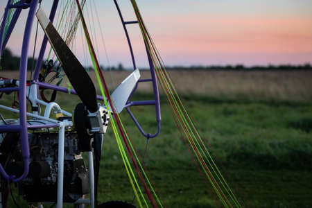 Closeup of a motorized paragliding trolley with a no-spin engine, propeller and colorful lines on the takeoff field on a beautiful evening. Extreme sports. Paragliding and small aircraft. Foto de archivo