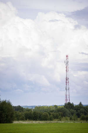 A telecommunications tower with radio and satellite dishes is installed in a rural area on a green field surrounded by trees. The concept of the harmlessness of electromagnetic and microwave Banque d'images