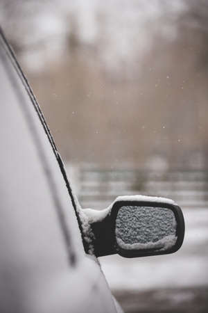 The first unexpected snowfall covered cars with snow. Rearview mirror in the snow. Traffic safety. Toning