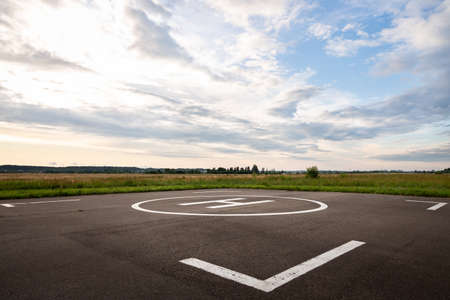 Hard surface for helicopter landing. Symbol for precise helicopter landing in the center. Evening landscape