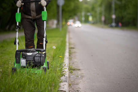 A worker in protective clothing with a gasoline lawn mower on wheels, mows the grass along the road. The powerful mower mows flowers and other plants. Territory care.