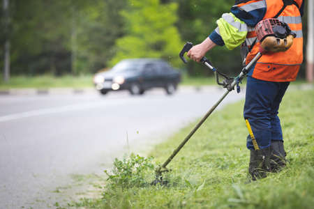 A worker in special reflective clothing with a gasoline mower in his hand. A man with a trimmer mows grass with dandelions on the side of the road Stock fotó