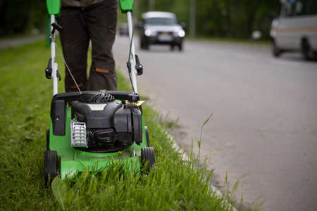 A front view of a worker wearing protective clothing and gloves walks alongside the road and mows the grass with a wheeled lawnmower. A man mows the grass on the side of the road against the background of passing cars.