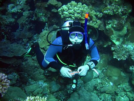 diver in deep with camera. underwater photographer photo
